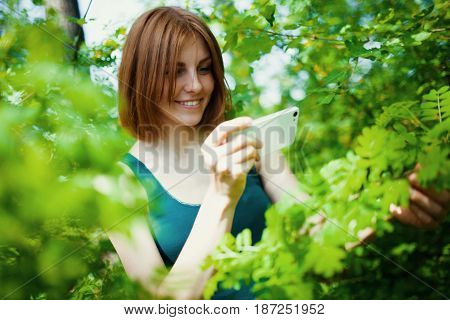 beautiful young woman make photo on cellphone, spring flowers background
