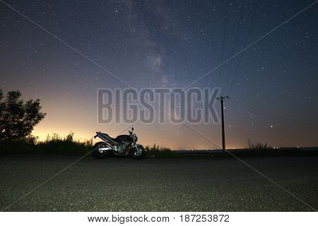 motorcycle under stars of  Milky Way galaxy