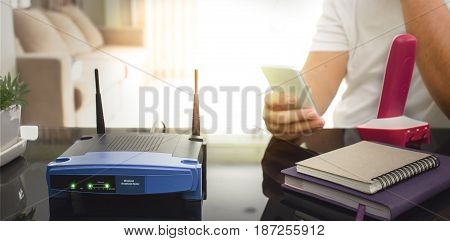 closeup of a wireless router and a young man using smart phone on living room at home