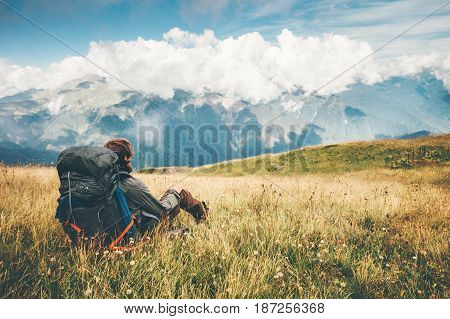 Traveler with backpack relaxing sitting on grass valley at mountains landscape Travel Lifestyle hiking concept adventure summer wanderlust vacations outdoor