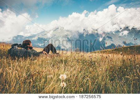 Man backpacker relaxing on grass valley at mountains landscape Travel Lifestyle hiking concept adventure summer wanderlust vacations outdoor