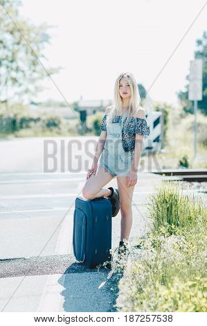 Beautiful young blonde girl smiling on the sunny road. Sitting on a suitcase luggage . Traveling the world with hitchhiking.