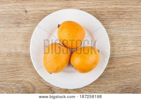 White Plate With Ripe Loquat On Wooden Table