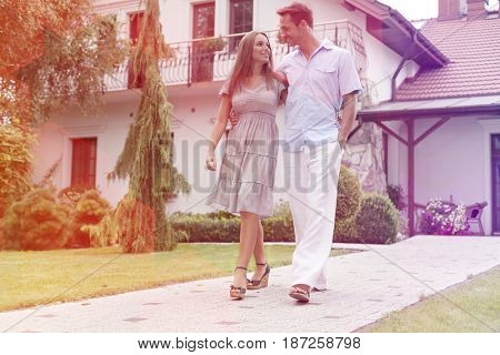 Full length of loving young couple walking on footpath in park