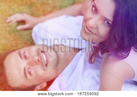 High angle portrait of playful young woman on top of man in park
