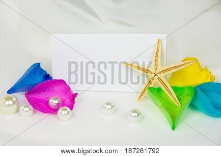 starfish and pearls on wedding tulle with rainbow rose petals and blank white card