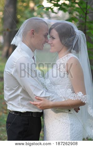 Young bride and groom posing for the camera outdoors in a park