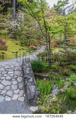 A rock bridge leads to blooming flowers in a Seattle garden.