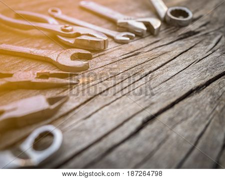 Dirty tools and equipments such as screw driver wrench plier on wooden background