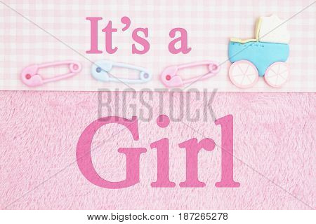 Old fashion It's a girl message Baby diaper pins and a baby carriage with pink fabric background and text It's a Girl