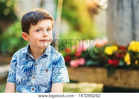 Outdoor summer portrait of adorable kid boy resting outdoors next to fountain on a very hot sunny day, wearing blue print shirt