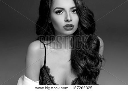 Young beautiful and sexy female model in black silk nightie and white coat sitting on white background. Fashion portrait. Stylish woman. Black and white