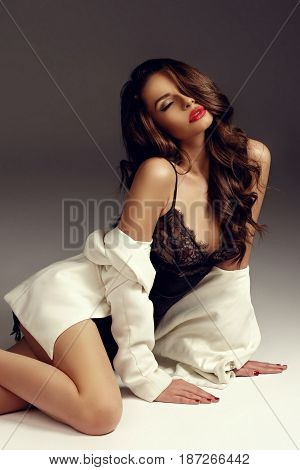 Sensual girl with long curly hair in black silk nightie, pumps and white coat sitting and posing on white background with closed eyes. Fashion vogue style portrait. Beautiful young woman