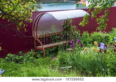 Metal bench seats have the canopy for protection against a rain is near a fence and near a flower bed.