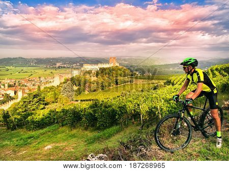Cyclist admires from the hill the Soave castle views.