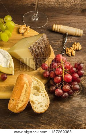 A photo of a bunch of grapes at a wine tasting, with slices of cheeses, a corkscrew, and a wine glass in the background, and a place for text
