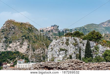 Distant view of Castelmola, Sicily Italy, a small colorful village close to Taormina, perched high on a rocky mountain on the skyline