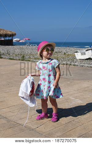 A little girl in a smart dress hat and glasses poses on the embankment in Batumi in the summer.