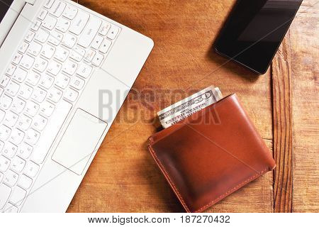 Working desk with white laptop, phone and wallet on the wooden table