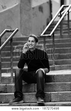 Young man talking on mobile while sitting on the stairs outdoors. Black-and-white photo.