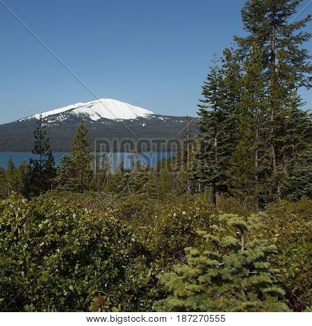View of the partially snow covered hills encompassing Diamond Lake in the Umpqua National Forest in Southern Oregon on a sunny spring day.