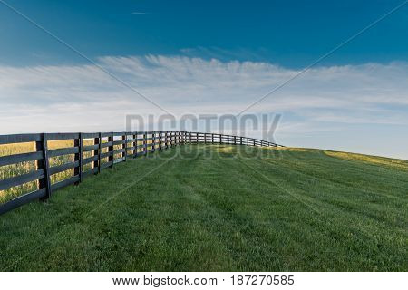 Black Fence Leads Over Grassy Hill