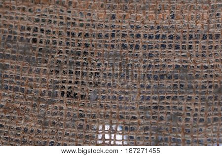 Texture of a burlap material. Hanging gunny net. Fabric background