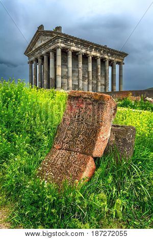 The temple of Garni. In the foreground is a carved stone with Christian symbols in the green grass.