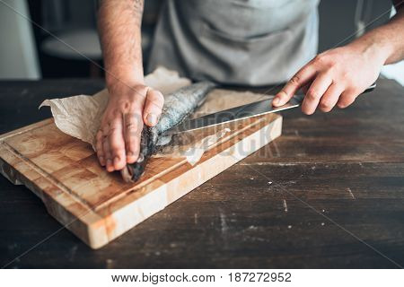 Chef hands with knife cut up fish on cutting board
