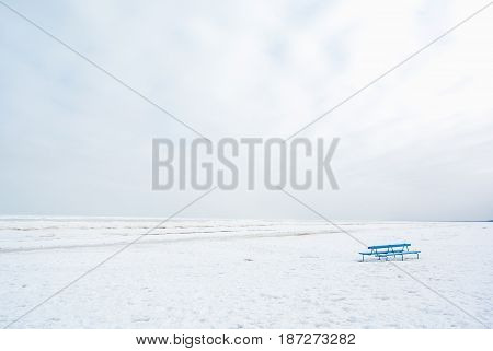 blue bench on the seashore white cold winter day