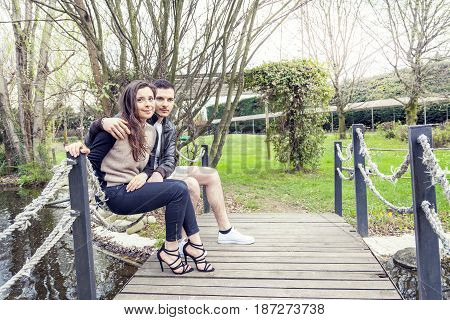 Nice Couple Of Boyfriends Embraces And Kisses On A Wooden Bridge