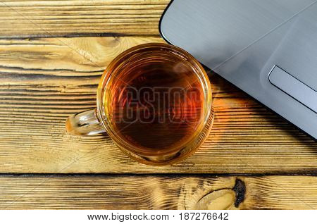 Laptop And Cup Of Tea On Wooden Table. Top View