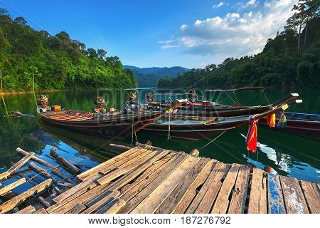 Vintage national boats on the lake surrounded by jungle. Sunset. Thailand.
