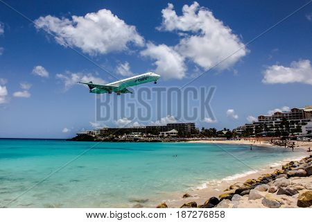 MAHO BAY BEACH  AUGUST 01: Airplane InselAir is landing on Princess Juliana International Airport, over Maho Bay Beach seen in St.Martin/St.Maarten on August 1, 2015
