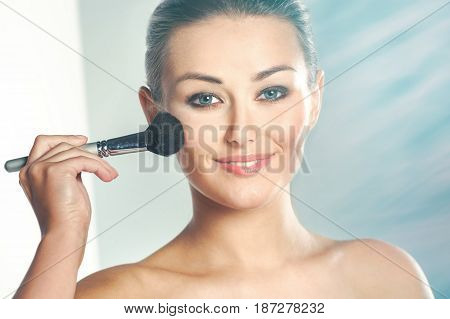Beauty Woman. Skincare concept. Beauty Face. Beauty concept.Makeup Applying. Professional Make-up.Beauty Fashion Girl Applying skin powder.