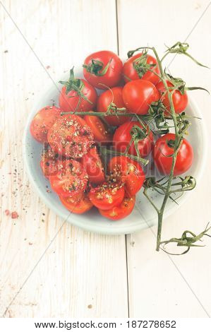 Fresh grape tomatoes with coarse salt for use as cooking ingredients with a halved tomato in the foreground over wooden background