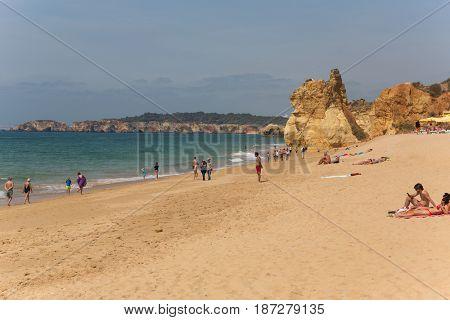 PRAIA DA ROCHA, PORTUGAL - APRIL 25, 2017: People at the beach of Praia da Rocha in Portimao. This beach is a part of famous tourist region of Algarve.