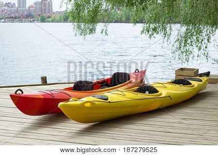 Two Kayaking Boats On Wooden Deck At Station Near Lake