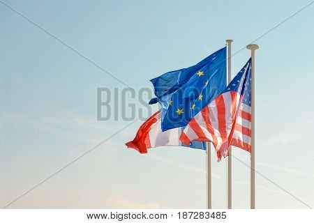 French American and European union Flags on blue sky