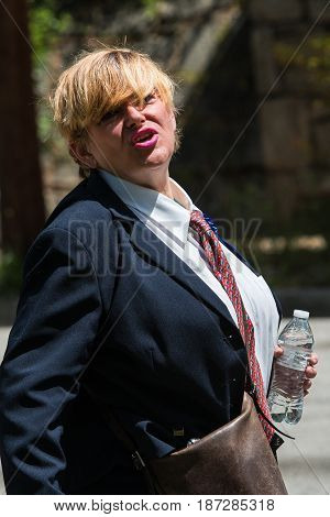 ATLANTA, GA - APRIL 2017: A woman in a man's suit impersonates President Trump after a rally at the Atlanta Tax March protesting President Trump not releasing his tax returns in Atlanta GA on April 15 2017.