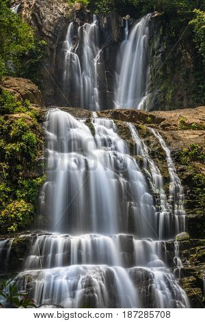 Double waterfalls in Costa Rica with grey rocks and green bushes and trees