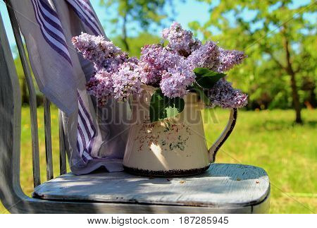bouquet of lilac in a jug on the old chair