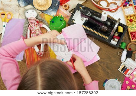 girl makes a dress template, top view, sewing accessories top view, seamstress workplace, many object for needlework, handmade and handicraft
