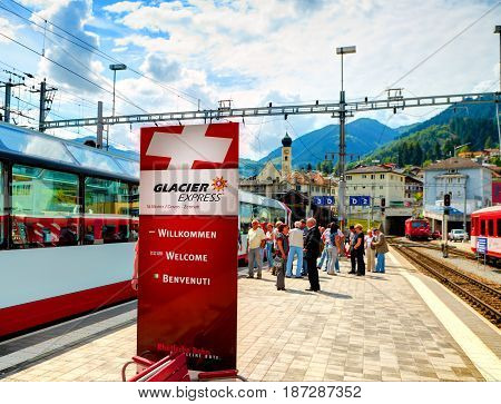 CHUR, SWITZERLAND, AUG, 20, 2010: View on Glacier Express panoramic mountain train advertising banner on Swiss rail way station, red mountain passenger train. Swiss holidays vacations travel tours