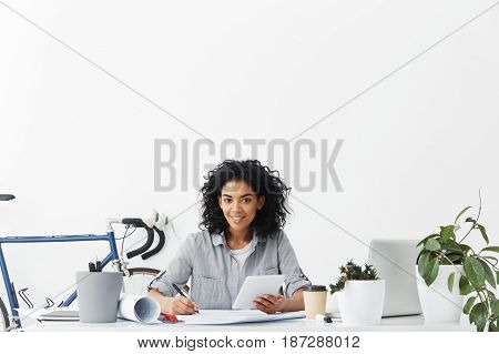 Indoor Shot Of Attractive Young African Student Architect Working At Her Project Work Holding Pen An
