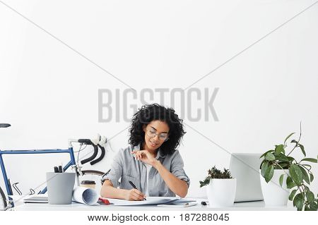 Horizontal Portrait Of Successful Young Dark-skinned Engineer Female Wearing Casual Shirt And Big Ro