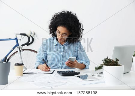 Concentrated Focused Afro American Female Freelancer Holding Phone In One Hand And Making Notes With