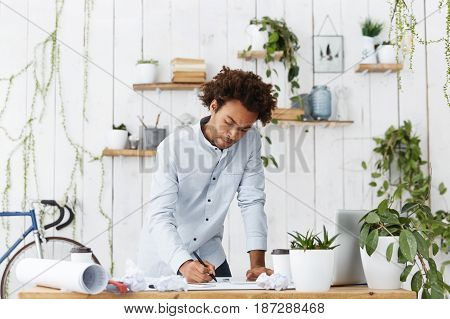 Skilled Professional Afro American Engineer Making Drawings Using Engineering Tools, Standing At His