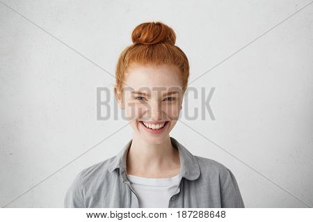 Head And Shoulders Of Cheerful Young Caucasian Woman In Good Mood Wearing Her Ginger Hair In Bun Poi