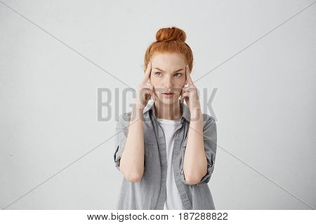 Studio Shot Of Serious Redhead Young Caucasian Woman Holding Fingers On Her Temples And Looking Up S